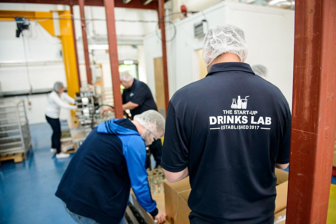 A staff member of The Start Up Drinks lab helps with the bottling process